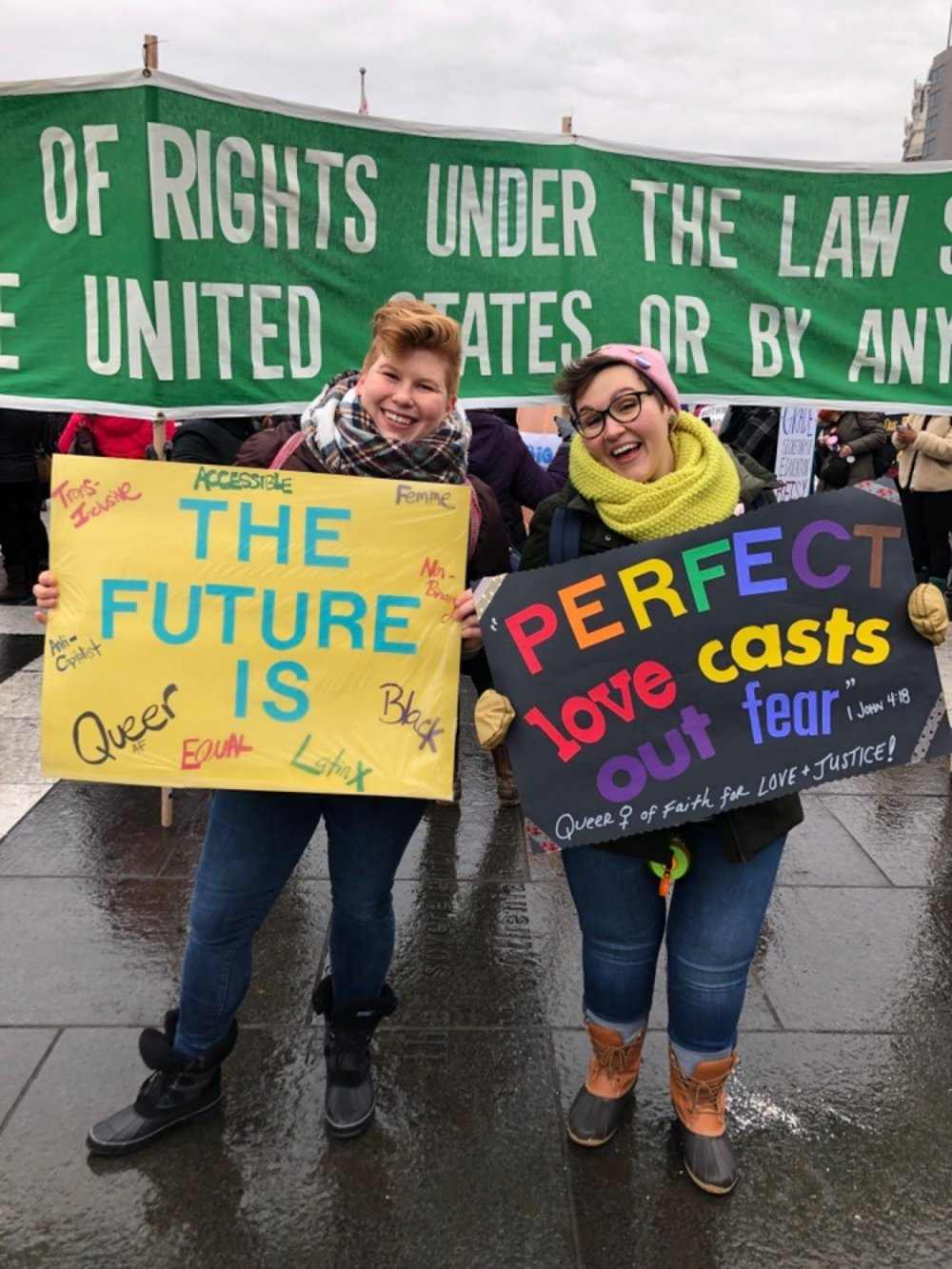 Two women smiling and holding activist signs.
