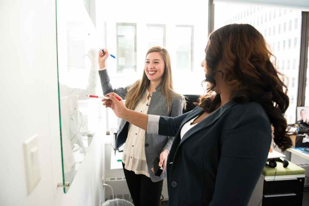 two women in front of dry erase board