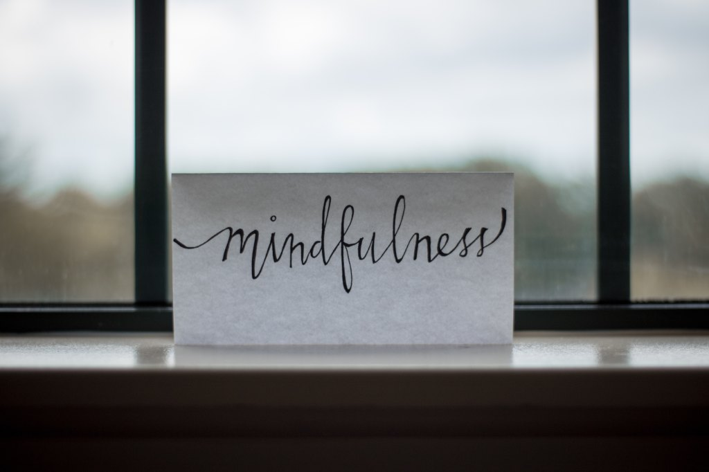 "A photo of a piece of paper leaning against a window. The paper has the word ""mindfulness"" written in cursive."