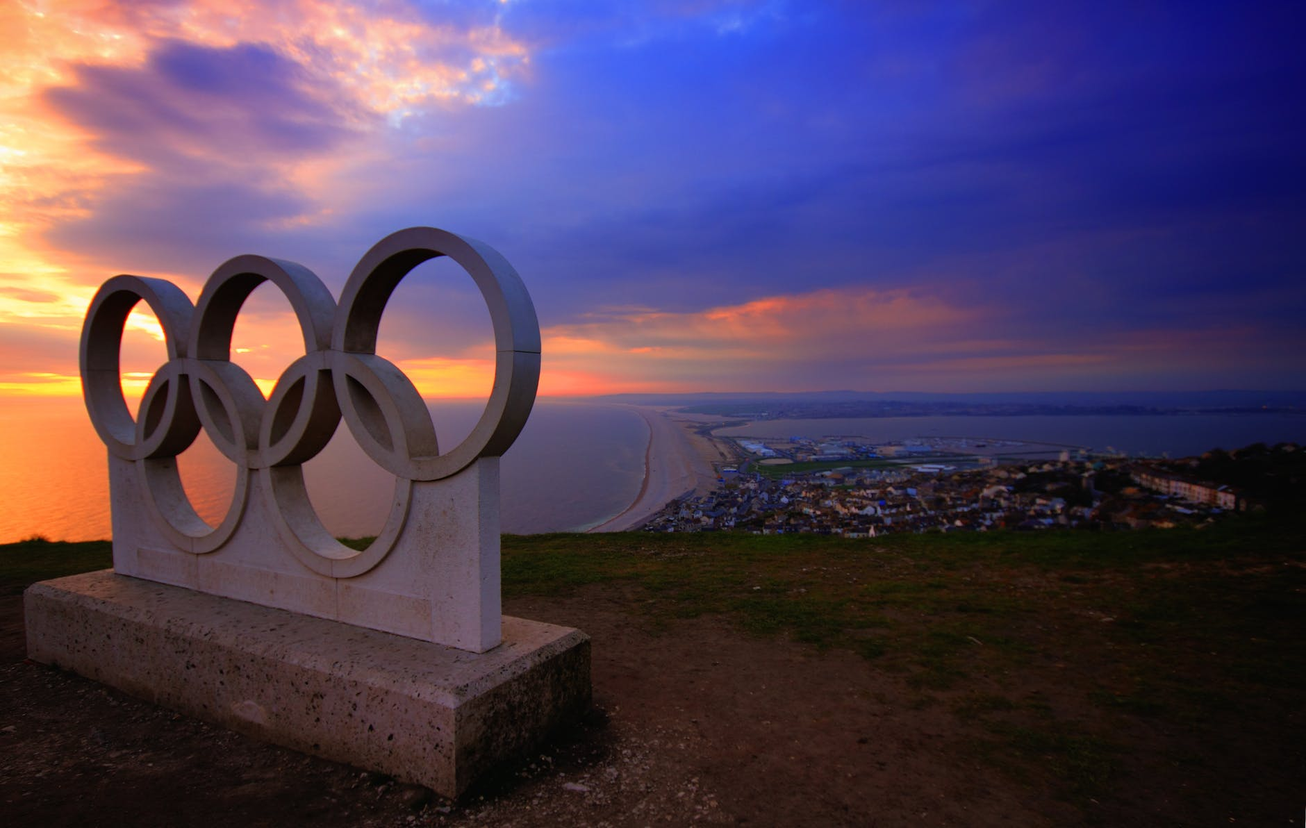 Image of the five olympic rings with a sunset in the background.