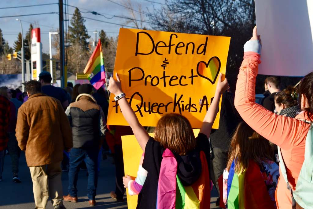"""picture of protestors marching for LGBTQ rights. Has a kid holding up a sign that says """"Defend and protect queer kids"""""""