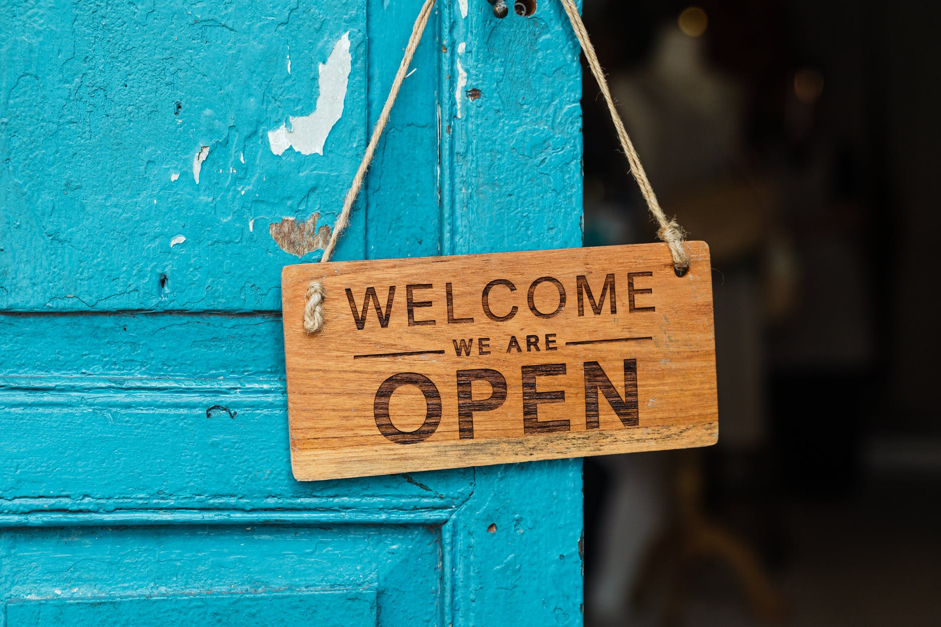 Image of sign on blue door reading WELCOME WE ARE OPEN.